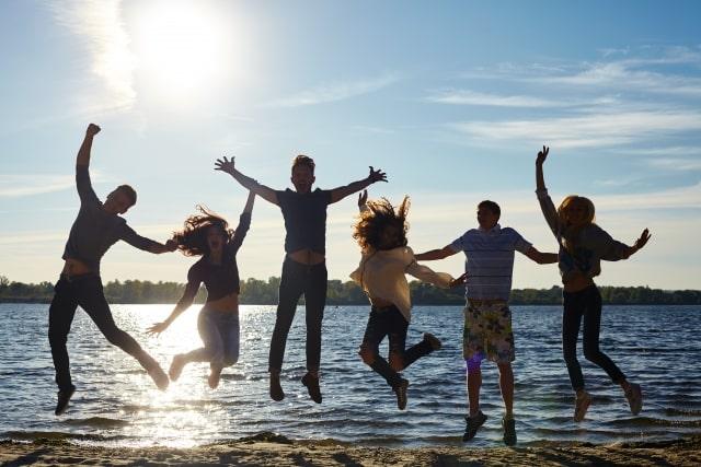 海辺でジャンプをする人たちの写真